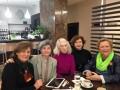 5 profesionales delante de una mesa tomando cafe.